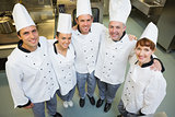 Five happy chefs smiling up at the camera