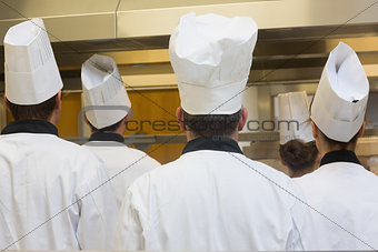 Five chefs standing in a kitchen
