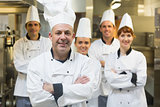 Five chefs wearing uniforms posing in a kitchen