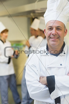 Smiling mature chef posing in a kitchen