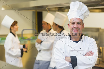 Mature male chef posing proudly in a kitchen