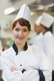 Female chef posing proudly in a kitchen