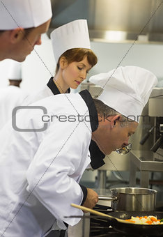 Male mature chef tasting some food