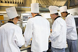 Four chefs working in industrial kitchen