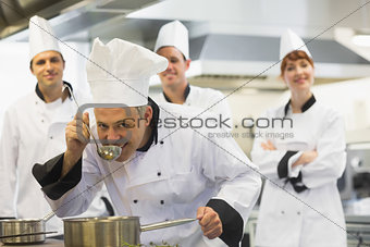 Head chef tasting a soup and smiling at camera