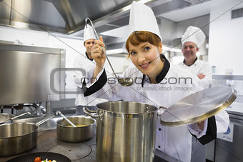 Young female chef tasting a soup