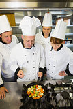 Experienced head chef explaining something to his colleagues
