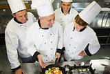 Experienced head chef showing pan to his colleagues