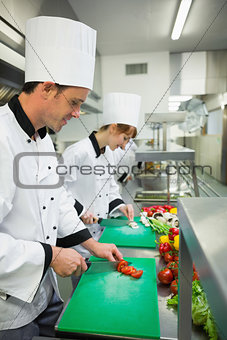 Two young chefs cutting vegetables