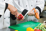 Close up of two chefs cutting vegetables