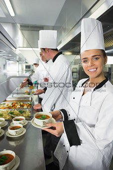 Smiling chef showing her soup