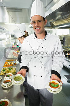 Young male chef presenting two types of soup