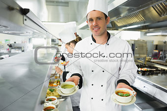 Happy chef presenting two types of soup
