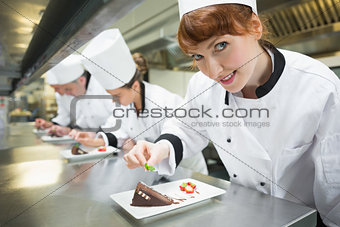 Smiling chef garnishing dessert plate