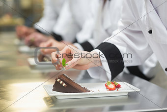Team of chefs in a row garnishing dessert plates