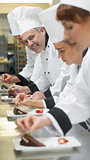 Team of chefs in a row garnishing dessert plates one smiling at camera