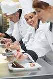 Team of chefs in a row garnishing dessert plates one girl smiling at camera