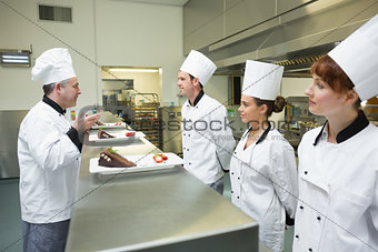 Three chefs presenting their dessert plates to the head chef