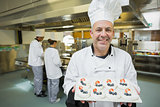 Smiling chef presenting proudly plate of meringues