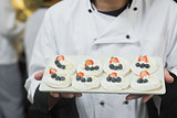 Chef presenting plate of meringues