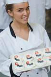 Smiling female chef presenting plate of meringues