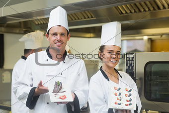Two proud chefs presenting dessert plates