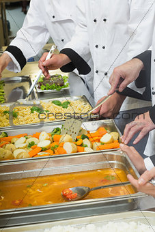 Chefs standing at serving trays of vegetables sauce and pasta