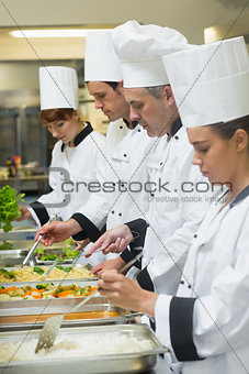 Four chefs working at serving trays