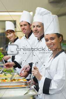 Four chefs working at serving trays smiling at camera