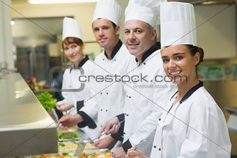 Four chefs smiling at camera while working at serving trays