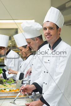 Happy chef standing at serving tray