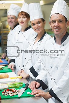 Four chefs standing in a row smiling at the camera