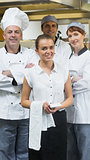 Waitress standing in front of team of chefs