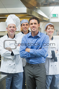 Handsome manager posing with some chefs