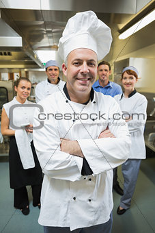 Head chef posing with his team behind him
