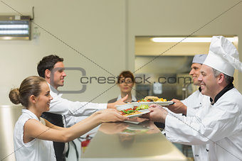 Two cooks handing plates to servers