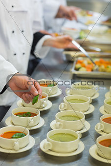 Bowls with soup being garnished