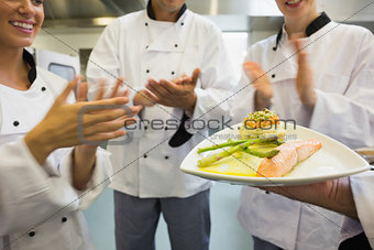 Young chefs applauding a salmon dish