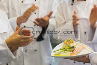 Chefs applauding a salmon dish