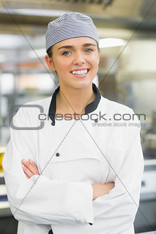 Young female chef posing with crossed arms