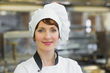 Happy female chef posing in a kitchen