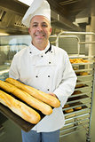 Mature baker presenting proudly some baguettes on a baking tray