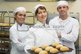 Three young bakers posing in a kitchen