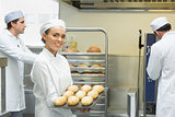 Cute young female baker holding a baking tray with rolls on it