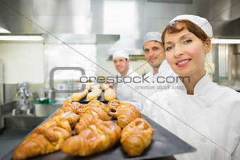 Three young bakers standing in a bakery