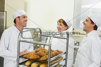 Three young chatting bakers standing in a kitchen
