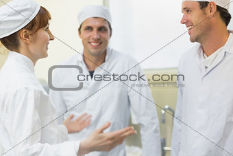 Young female baker talking to her colleagues