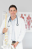 Handsome smiling doctor holding skeleton model