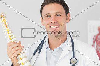 Handsome happy doctor holding skeleton model