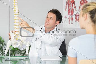 Handsome doctor showing a patient something on skeleton model